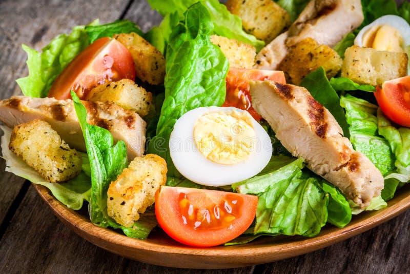 凯萨色拉用油煎方型小面包片、西红柿和烤鸡关闭 免版税库存照片