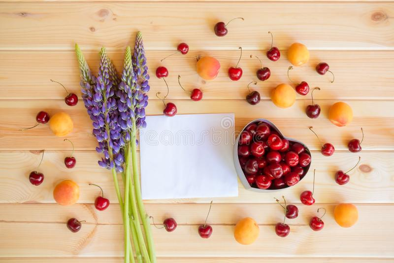 凶猛您的文本、蓝色的野花,心形礼物盒用新鲜的樱桃和新鲜水果的空的卡片 免版税库存图片