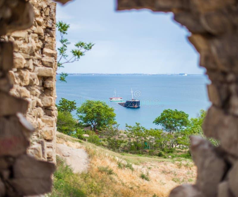 凹下去的船的看法通过在石墙o的漏洞 库存图片