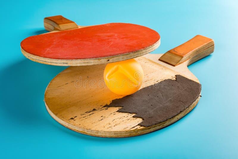 凹痕乒乓球和对在蓝色的球拍 免版税库存照片