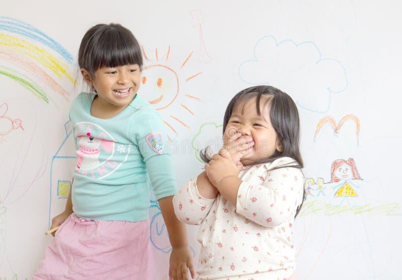 凹道的两个小微笑的孩子在墙壁上 库存照片