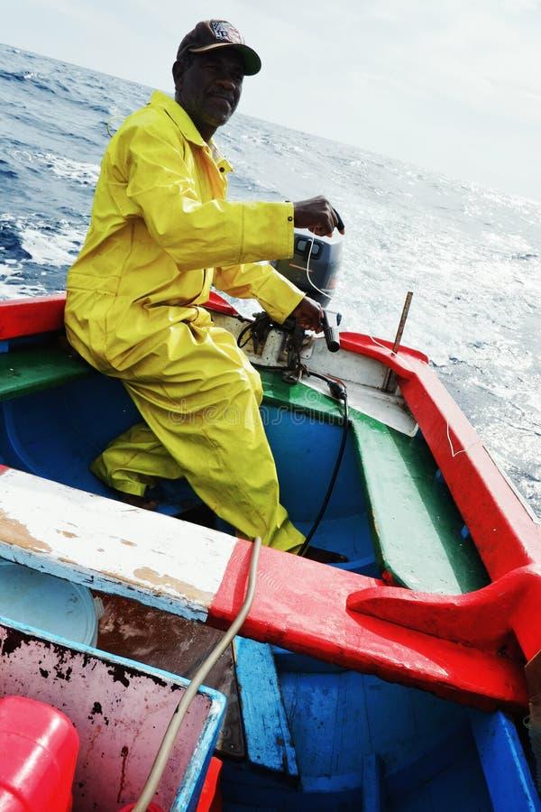 出去对海的地方渔夫为黄色飞翅金枪鱼或嗬钓鱼在一艘传统五颜六色的充气救生艇 免版税库存图片