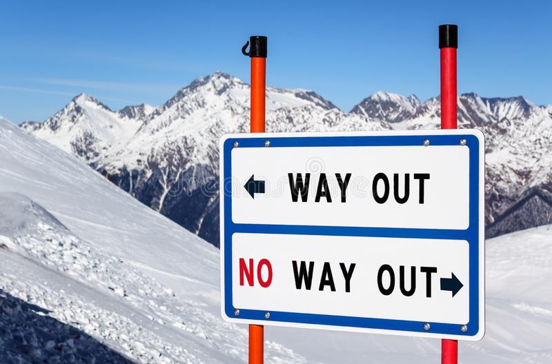出口对在滑雪场的没有出口信息方向标分枝的小河反对多雪的山峰和天空蔚蓝冬天 免版税库存图片