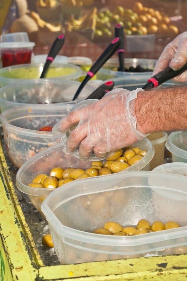 出售商挖出的橄榄的手到一个容器里在农夫市场上 免版税图库摄影