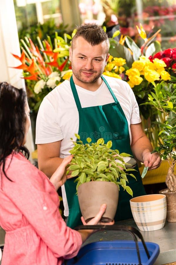 出售盆的工厂花的微笑的男性卖花人 图库摄影