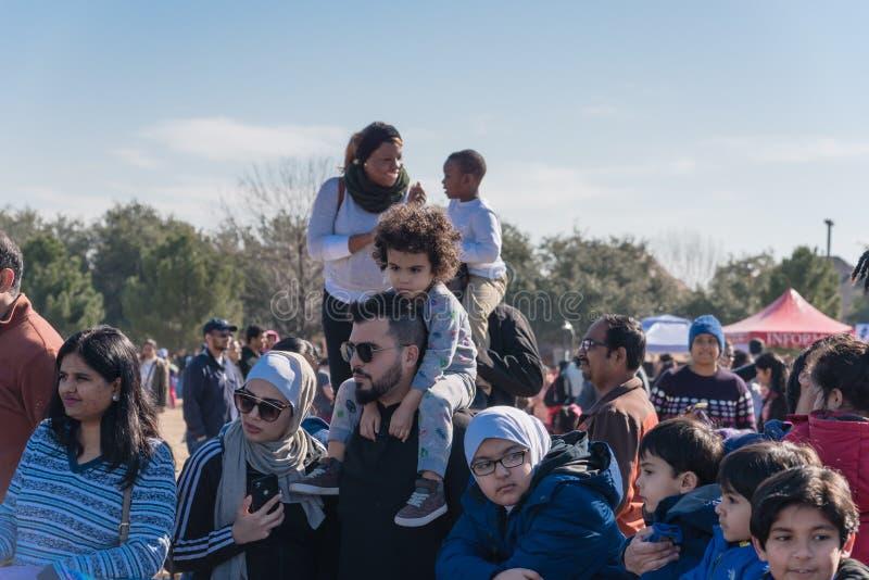 出席室外冬天节日的肩扛乘驾的孩子在欧文,得克萨斯 免版税库存图片