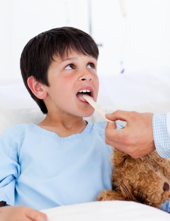 出席少许医疗男孩逗人喜爱的检查 免版税库存照片
