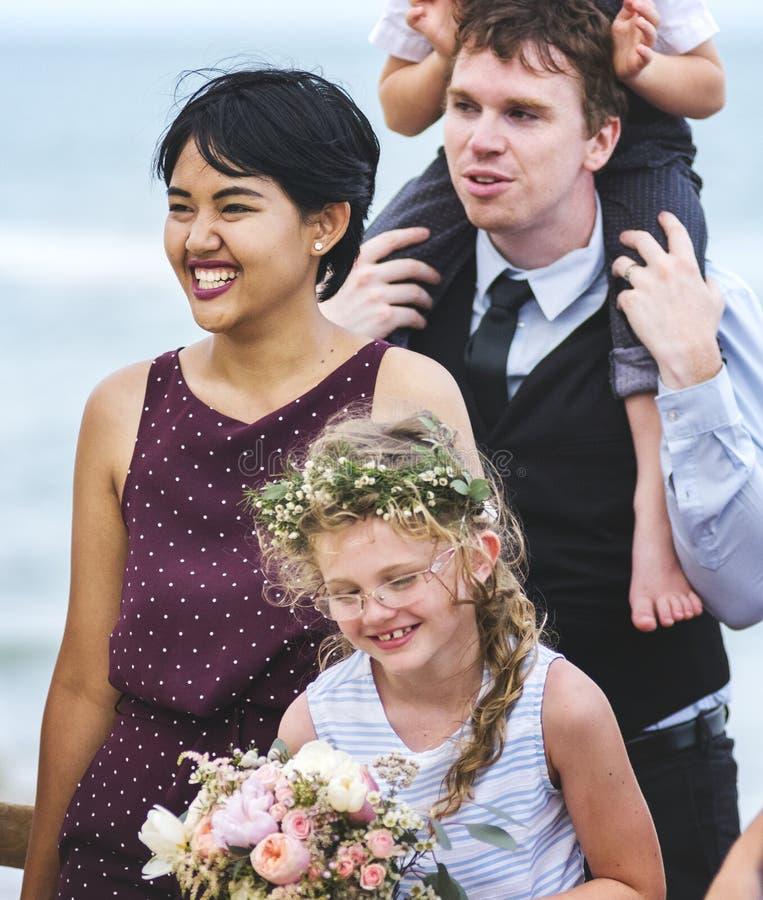 出席海滩婚礼仪式的人们 免版税库存图片