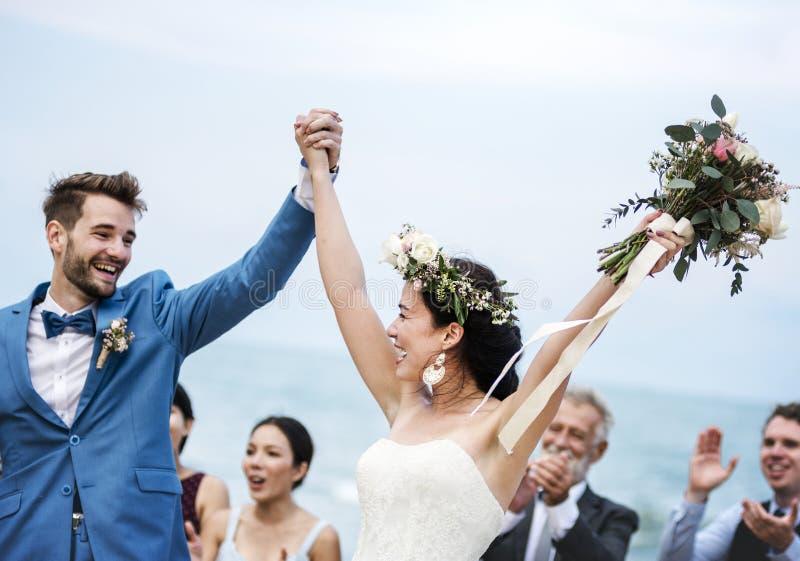 出席海滩婚礼仪式的人们 免版税图库摄影