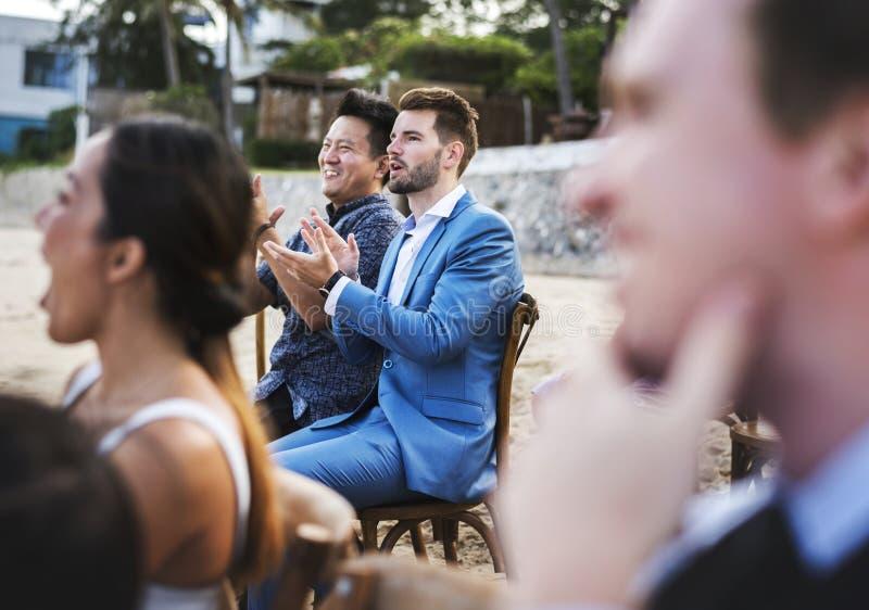 出席海滩婚礼仪式的客人 免版税库存照片
