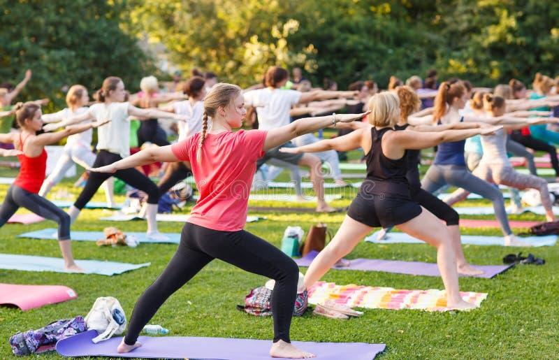 出席瑜伽班外部的大小组成人在公园 免版税库存照片