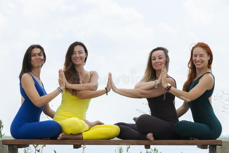 出席瑜伽班外部的小组成人在公园 免版税图库摄影
