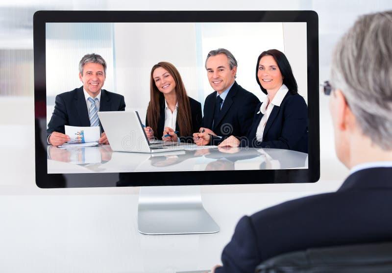 出席电视电话会议的成熟商人 免版税库存照片