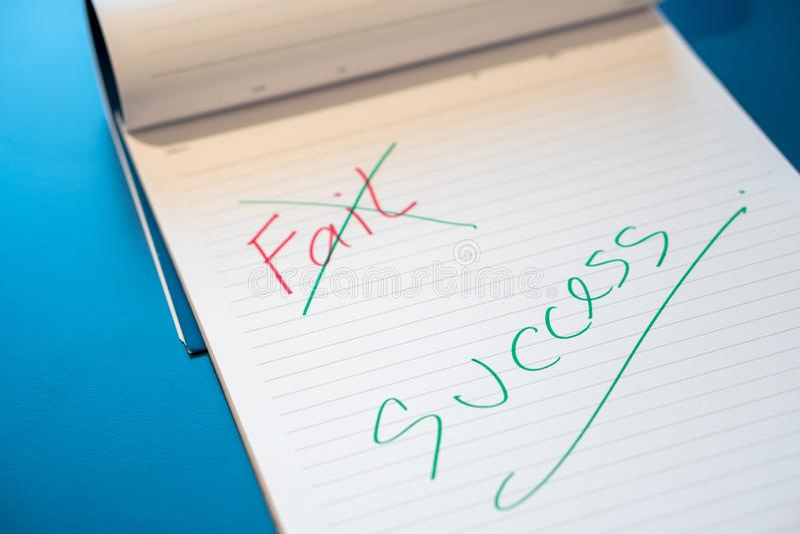 出故障文本用有一支红色笔的一只手并且注销了与在笔记本的一支绿色笔 用手成功消息与一绿色penFai 图库摄影