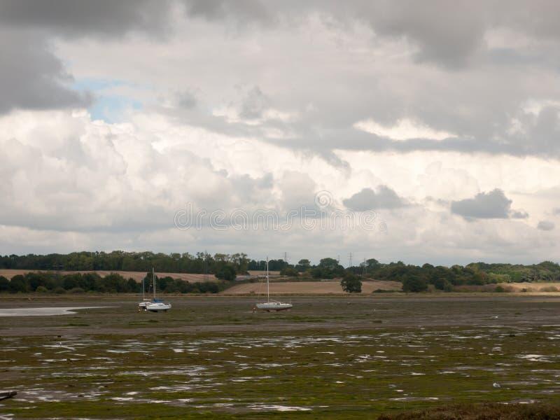 出海口场面浪潮小船停泊了manningtree阴云密布 库存图片