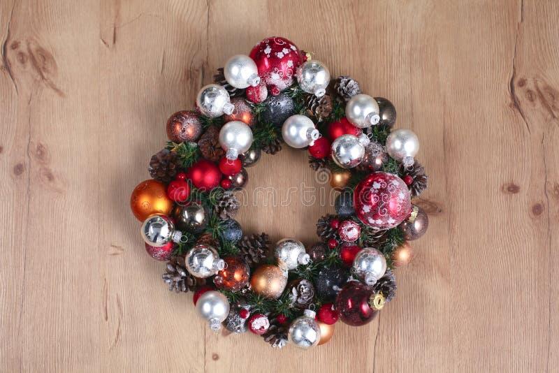 出现在木门装饰的圣诞节花圈 免版税库存照片