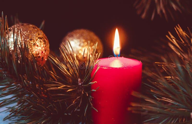 出现花圈的红色灼烧的蜡烛与冷杉分支和金黄圣诞节球的在黑背景 免版税库存照片