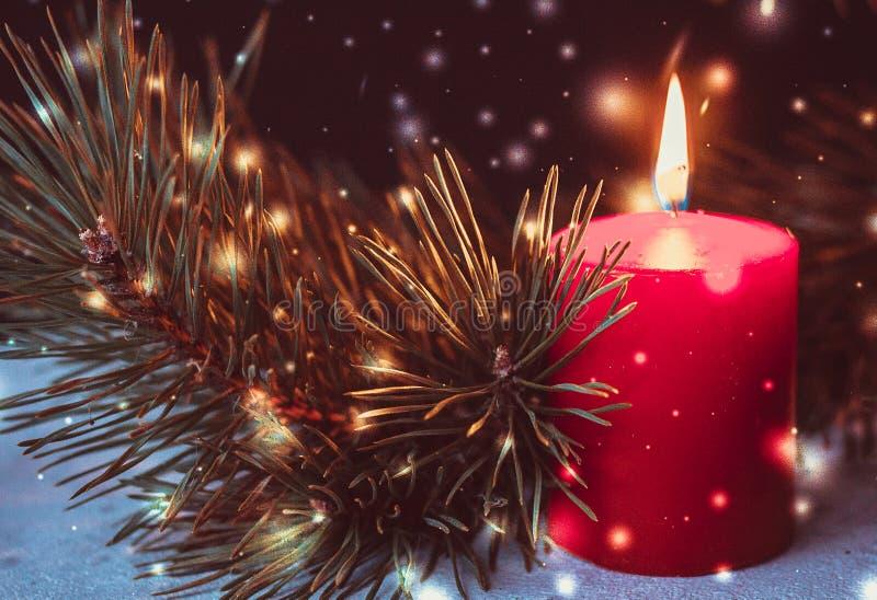 出现花圈的红色灼烧的蜡烛与冷杉分支和金黄圣诞节球的在黑背景 免版税图库摄影