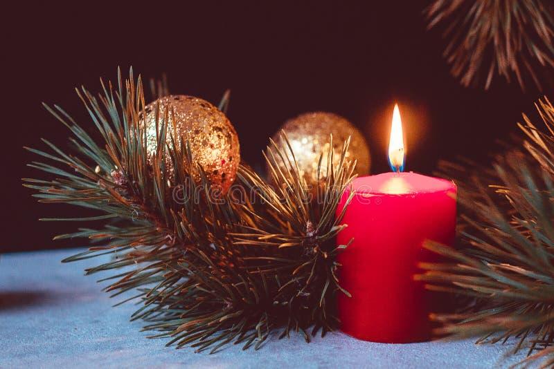 出现花圈的红色灼烧的蜡烛与冷杉分支和金黄圣诞节球的在黑背景 库存图片