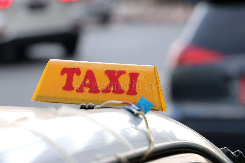 出租汽车光标志或小室在与红色文本的黄色颜色签字在汽车屋顶在街道被弄脏的背景 免版税库存照片