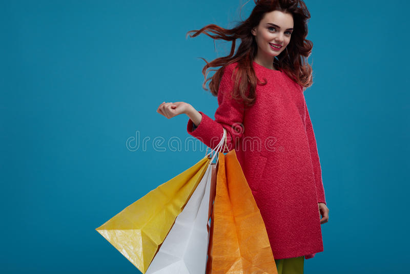 出色的女孩购物年轻人 与纸袋的微笑的美好的时装模特儿 免版税库存图片