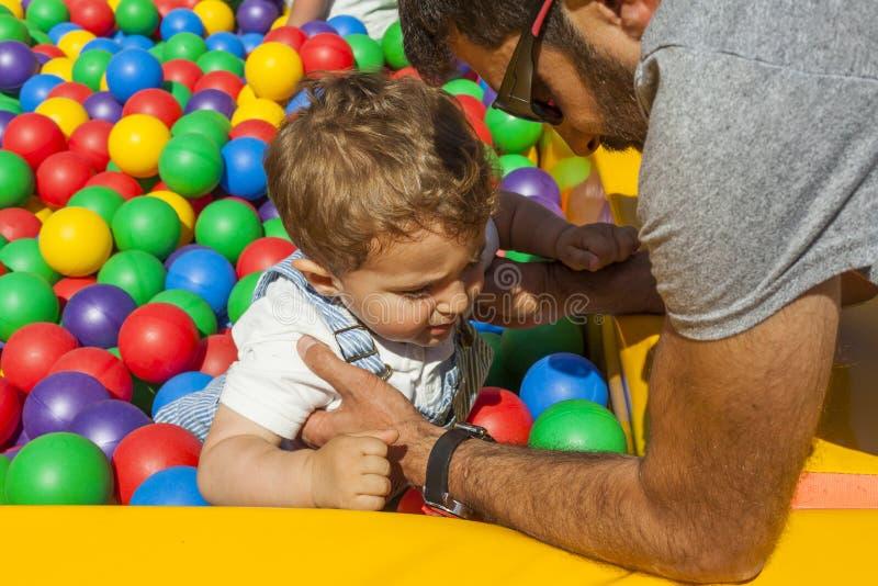 出去一个五颜六色的塑料球水池的爸爸帮助的男婴 库存图片