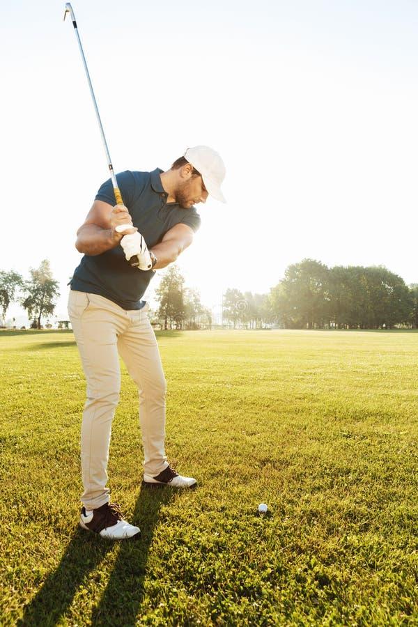 击中与俱乐部的年轻男性高尔夫球运动员球 免版税库存照片