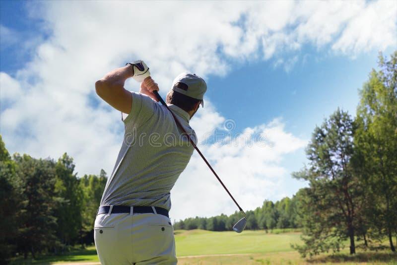 击中与俱乐部的高尔夫球运动员高尔夫球球击在路线,当在度假暑假时 免版税库存照片