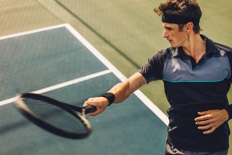 击中从基础线的网球员正手击球 图库摄影