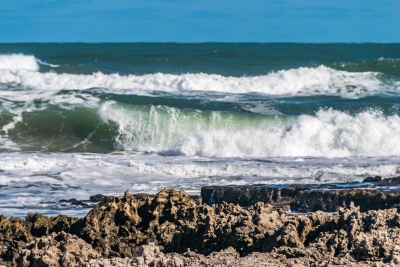 击中在石头的海波浪在海岸白色泡沫附近从海波浪的波浪白色泡沫出来 库存照片