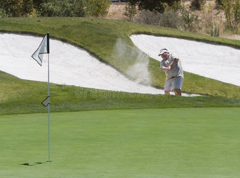 击中地堡的高尔夫球运动员  图库摄影