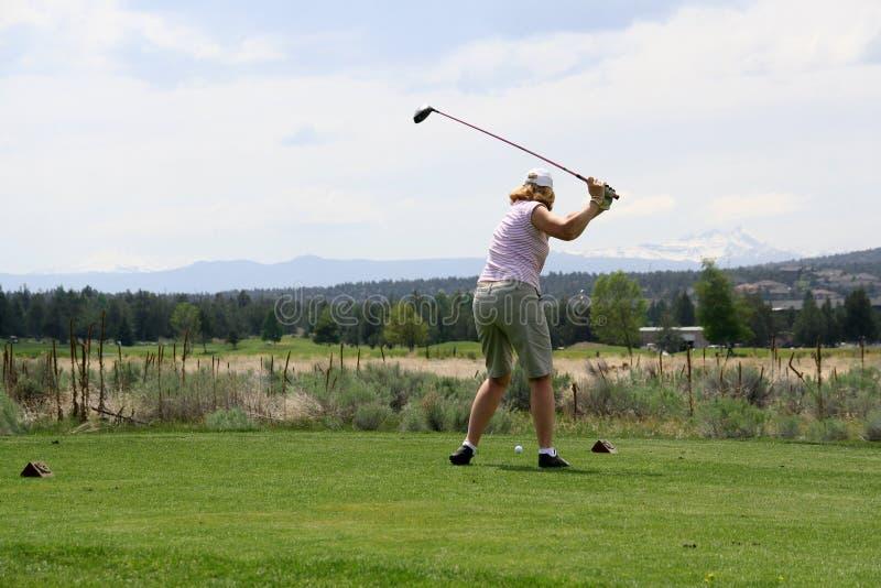 击中夫人的球高尔夫球运动员 图库摄影