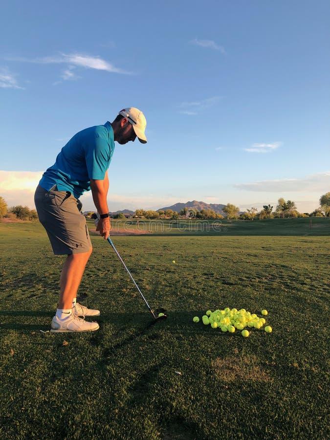 击中实践的高尔夫球运动员高尔夫球从后面看法 免版税库存图片
