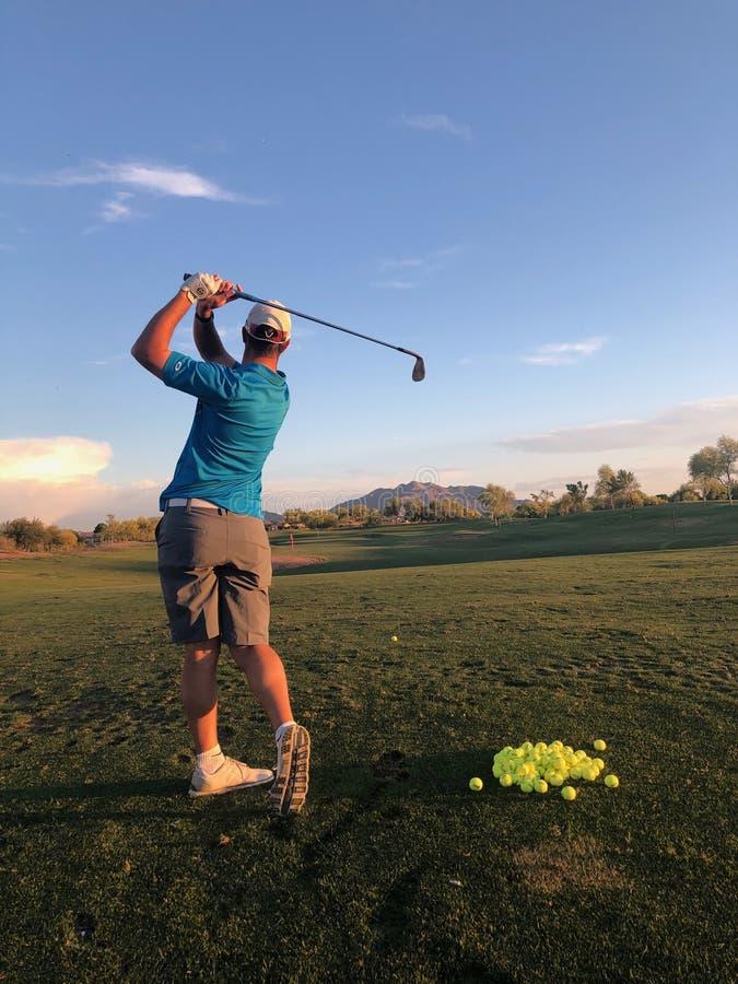击中实践的高尔夫球运动员高尔夫球从后面看法 免版税库存照片