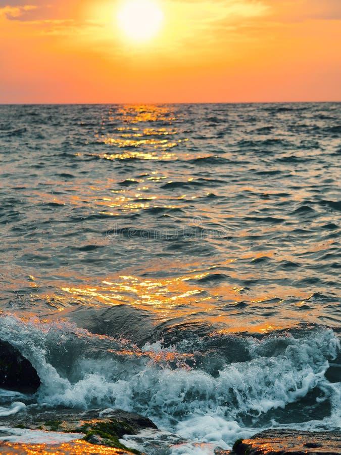 击中岩石岸的波浪在日落 库存图片