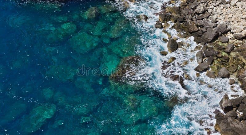 击中岩石的透明的蓝色波浪空中顶视图创造白色泡沫 库存图片