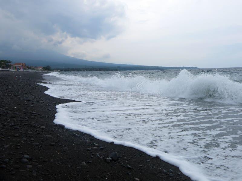 击中巴厘岛的含沙黑火山的沙滩波浪、海浪和海泡沫 在Amed,海是安静,但是在附近的波浪 库存图片