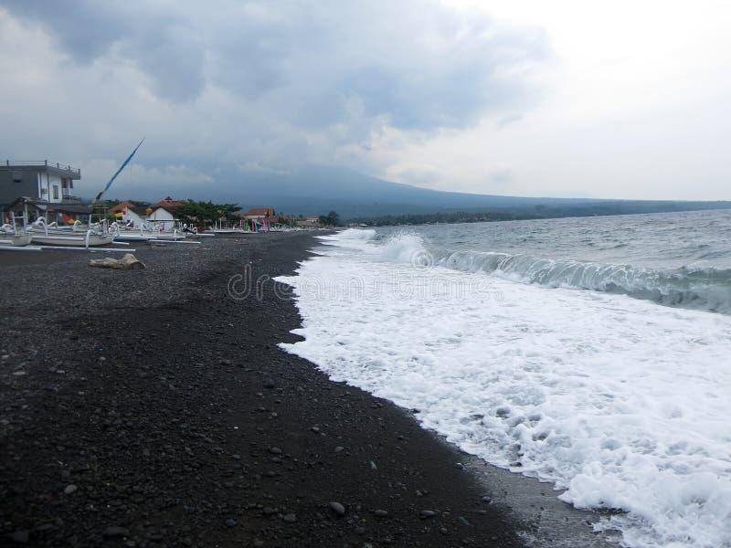 击中巴厘岛的含沙黑火山的沙滩波浪、海浪和海泡沫 在Amed,海是安静,但是在附近的波浪 免版税图库摄影
