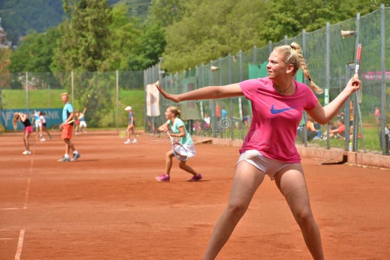 击中正手击球的用左手的女性少年网球员 库存照片