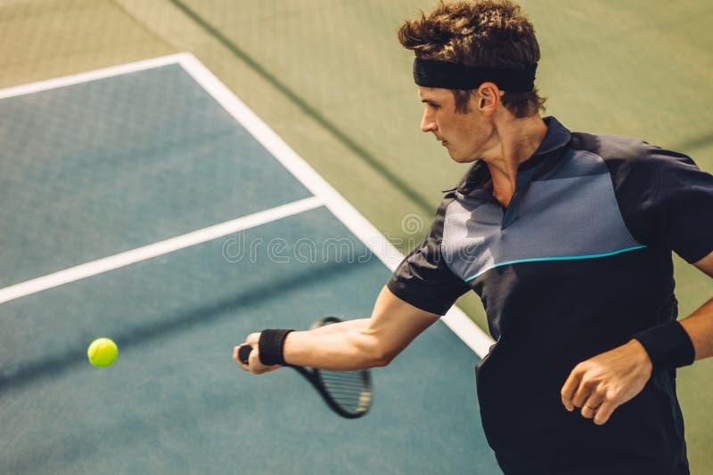 击中正手击球的职业网球球员 免版税库存图片