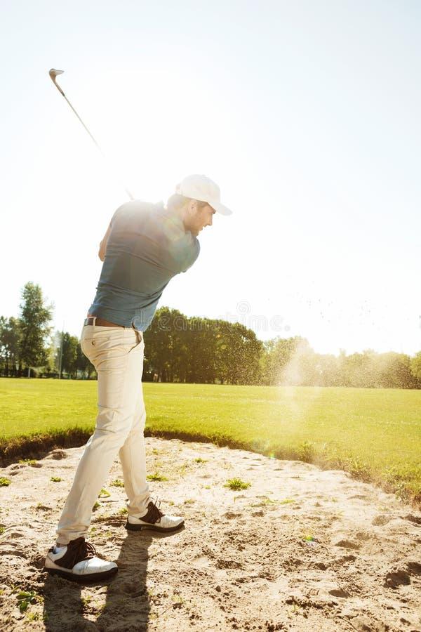 击中球的男性高尔夫球运动员在砂槽外面 免版税库存图片