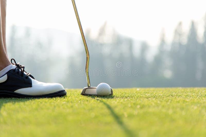击中球的高尔夫球区的高尔夫球运动员妇女入一个孔在假日晴天 库存照片