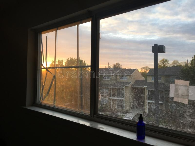 击中窗玻璃的忧郁日落 免版税库存图片