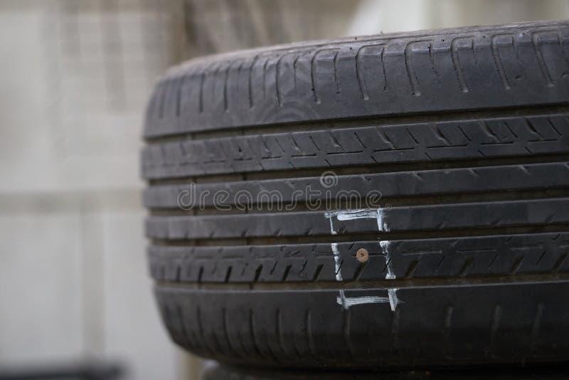 击中钉子或锋利的对象损坏在地板上的轮胎,造成橡胶漏出,并且不可能跑 免版税图库摄影
