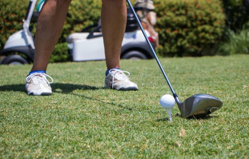 击中高尔夫球的高尔夫球运动员发球区域 库存照片