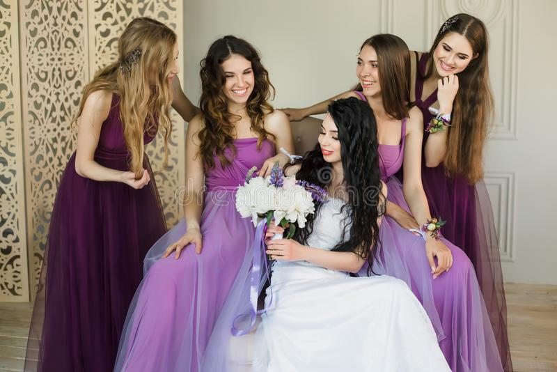 击倒被激发关于婚礼 微笑可爱的年轻的新娘拿着婚礼花束和,当谈话与她时 库存图片