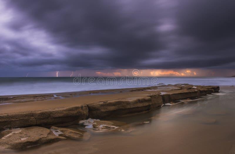 击碎在岩石和剧烈的天空的波浪与闪电在科孚岛希腊 库存图片