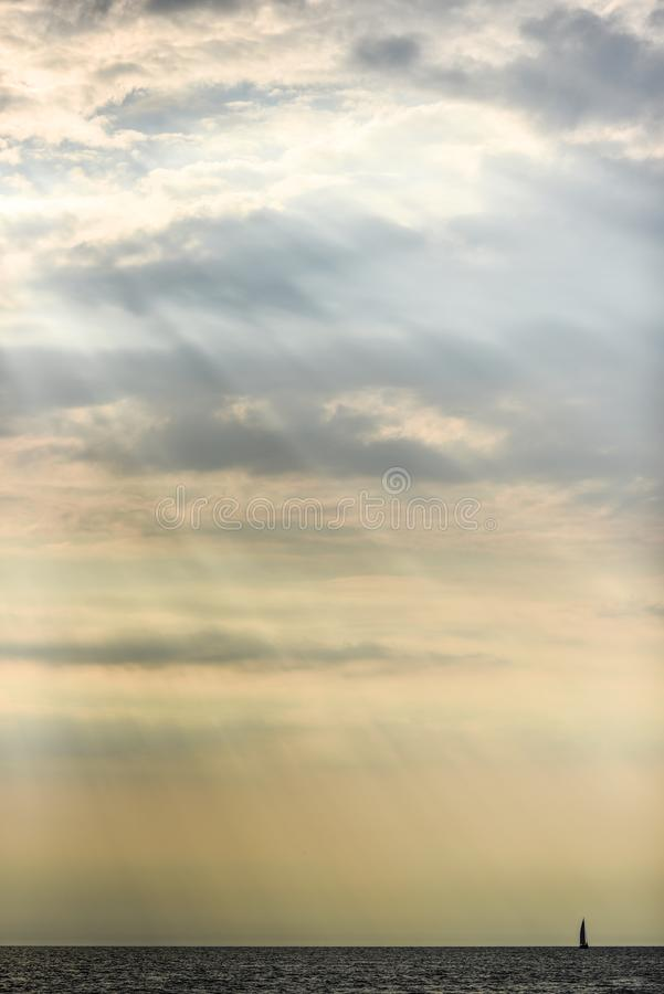 击穿在海,小船的太阳的光芒云彩 免版税库存照片