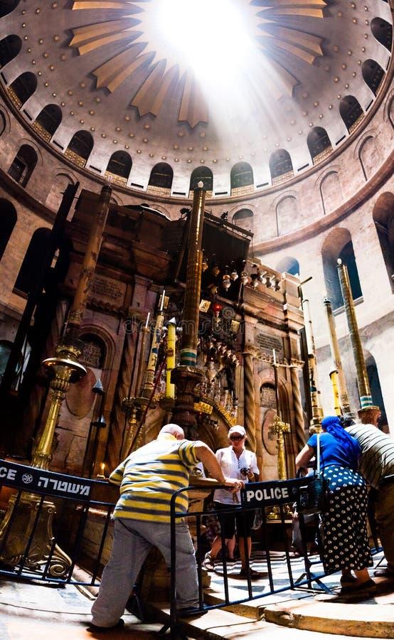 击穿的太阳光芒通过圆形建筑在aedicula的圆顶在圣洁坟墓的教会里在有访客的耶路撒冷 库存照片