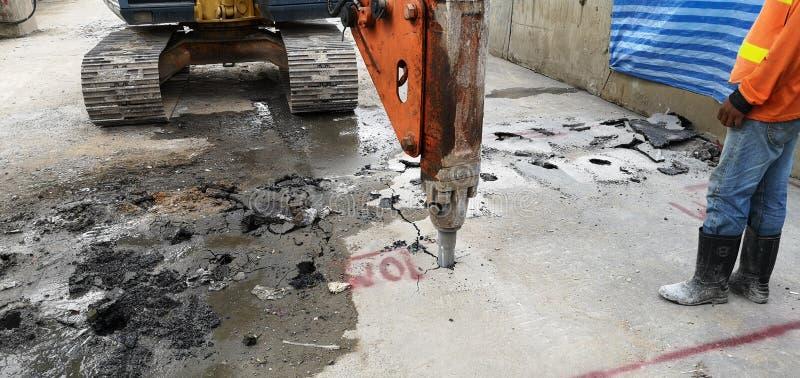 凿岩对做爆破的汽车工作具体与工作者在站点在曼谷泰国天空火车 图库摄影